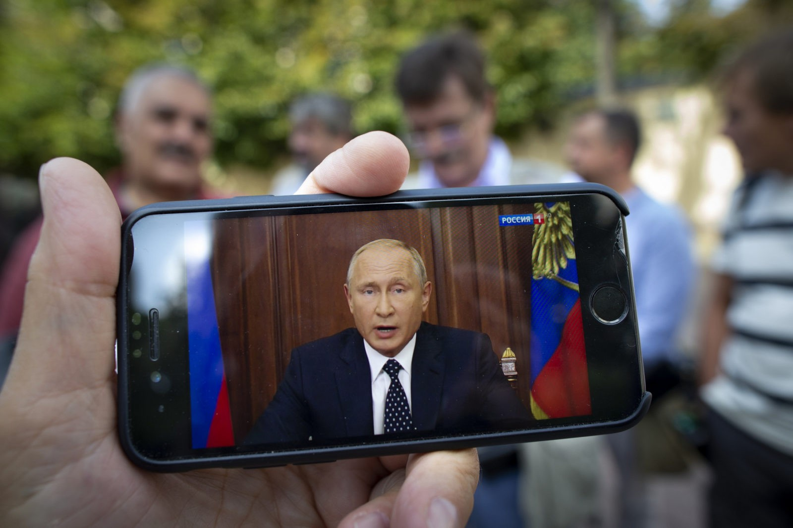 """People stand in a street in Moscow, Russia, Wednesday, Aug. 29, 2018, as Russian President Vladimir Putin addresses on state TV. Putin in a televised address Wednesday said without raising the retirement age Russia's pension system """"would crack and eventually collapse."""" He offered concessions to the reform, saying that women's retirement age should increase from 55 to 60 years, lower than had proposed. (AP Photo/Alexander Zemlianichenko)"""